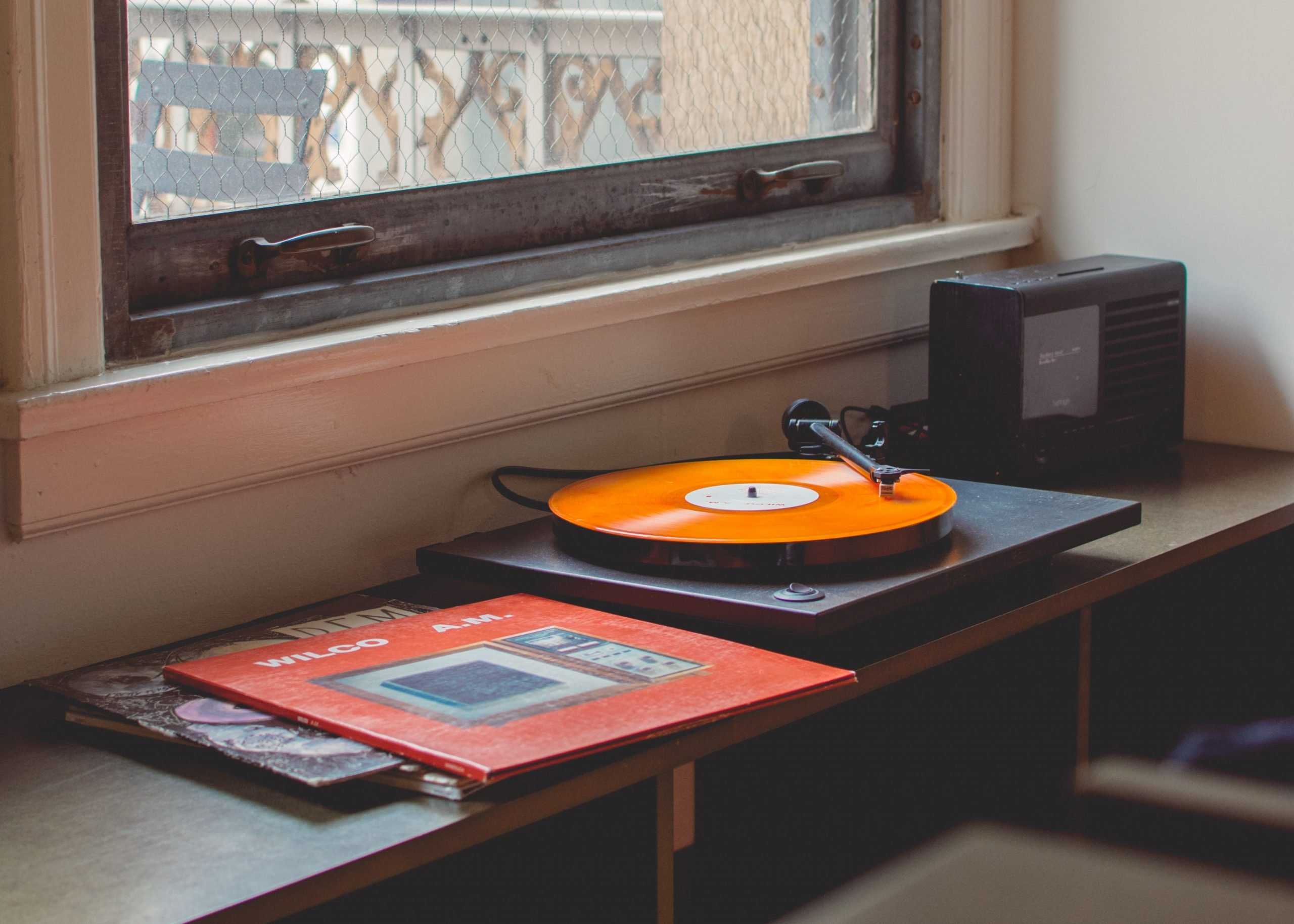 A reocrd player sitting on a table spinning an orange record