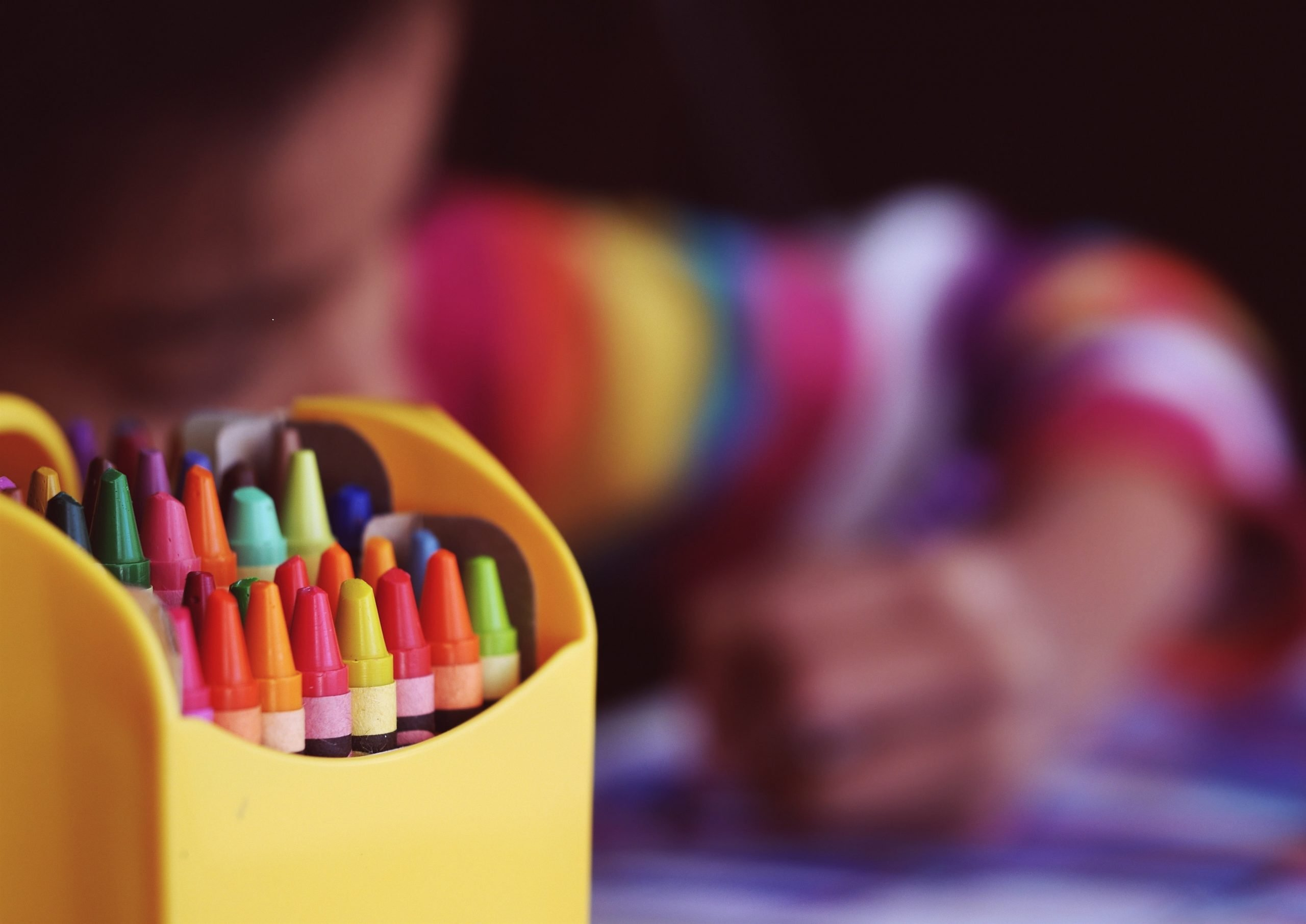 Focus on a pack of coloured crayons and a child blurred in the background drawing