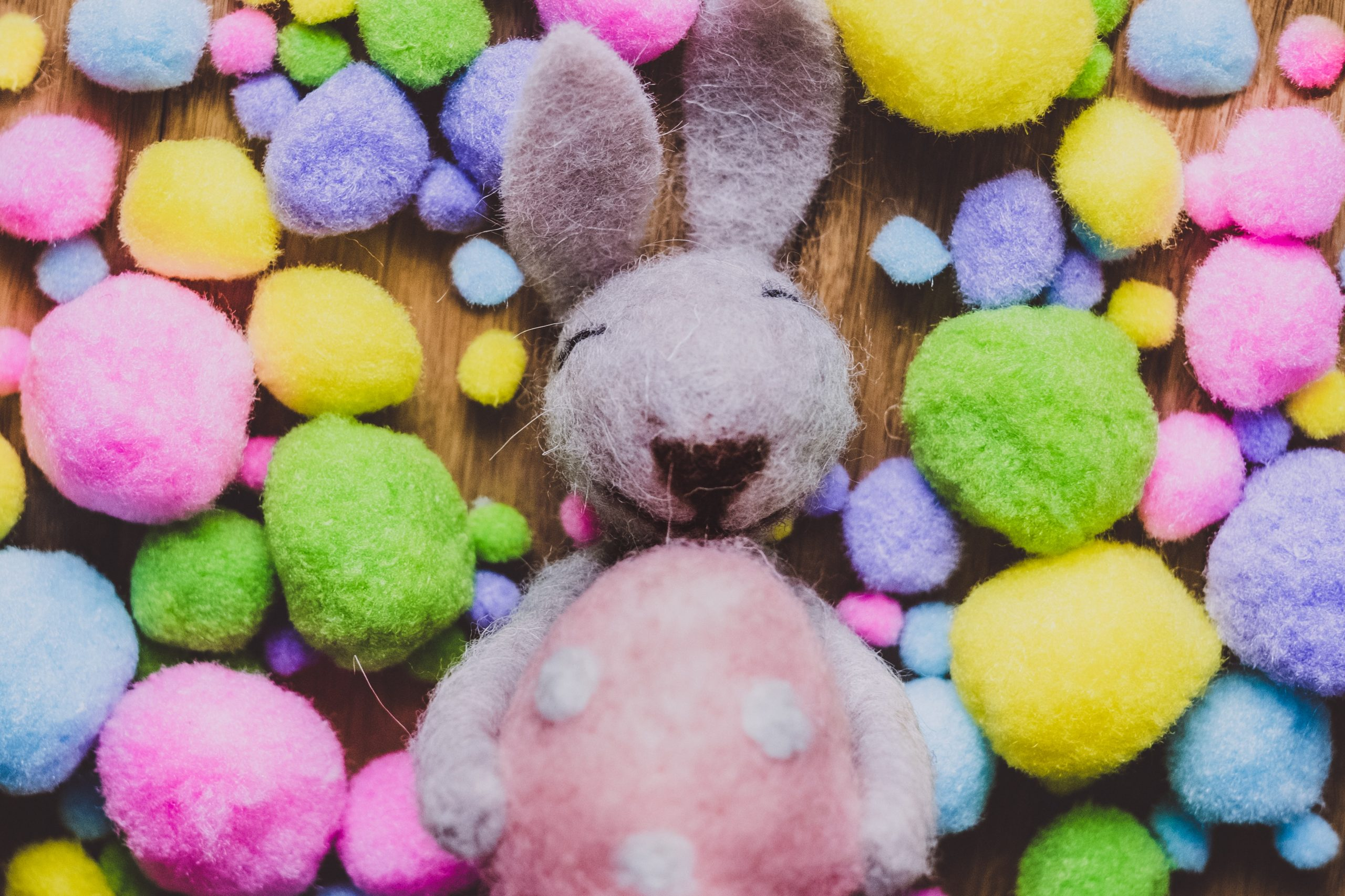 A felt made Easter bunny on a table surrounded by a number of pom poms looking like Easter eggs
