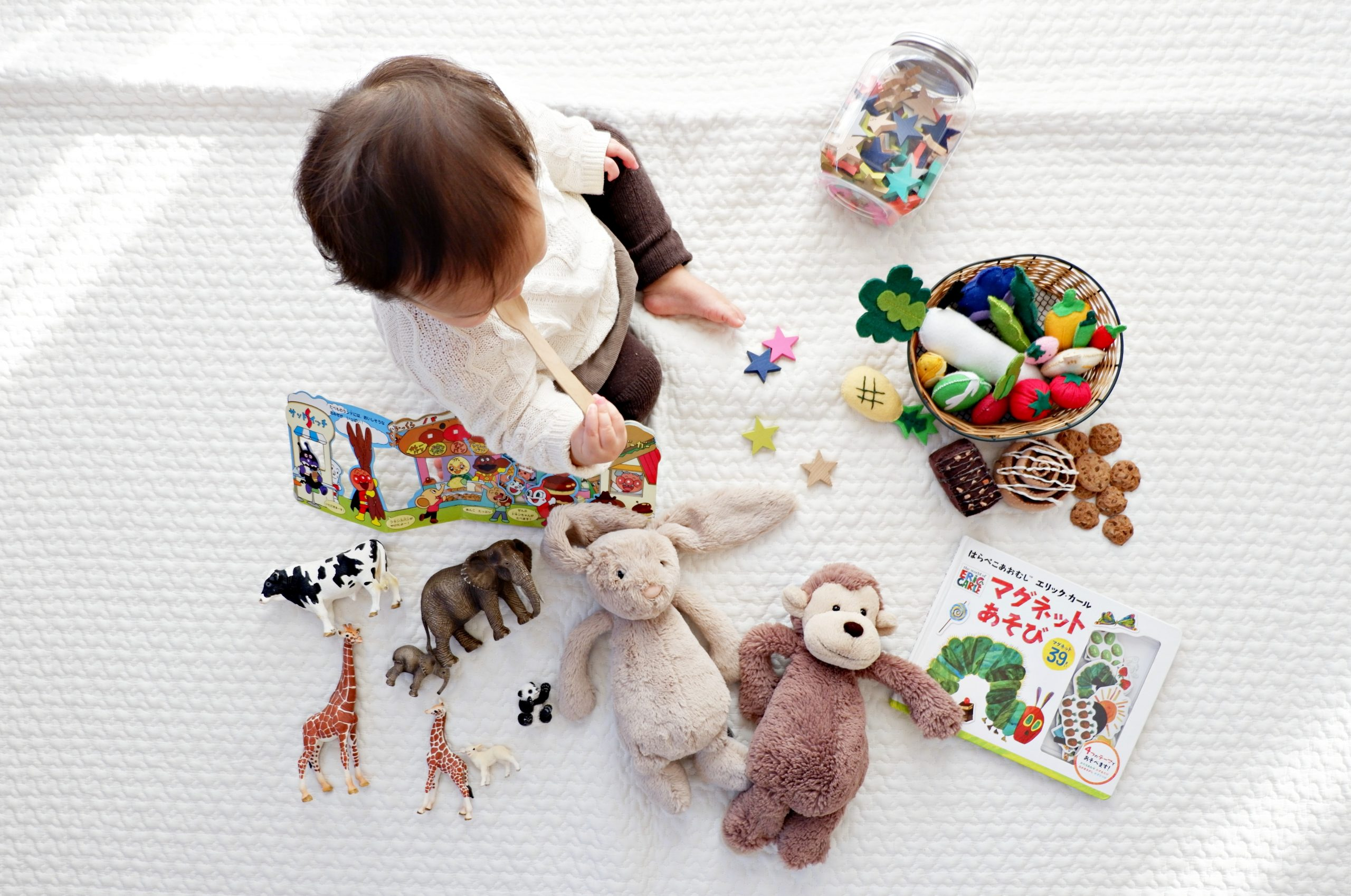 A top down view of a small toddler sitting on a white sheet and surrounded by various different toys